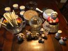 Twelve (12) Pcs. Salt and Peppers, GUILDCRAFT New York Cake Tin, Creamer, Sugar, Fondue Set, Lidded Glass Candy Dish, & Grandma Cookie Jar & FIRE KING