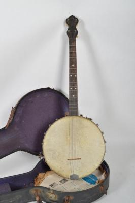 One (1) Four String Steel Back Banjo with a Purple Cloth Lined Hard Case. Condition is Midline Steel Back has a Crack and Some Surface Scratches.