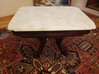Marble Rectangular Side Table Carved Walnut Center Table, Circa 1890. Features a Beveled Marble Top Surmounting Carved Walnut Base.