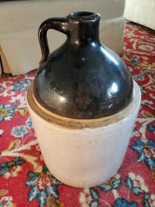 "Vintage Stoneware Jug - This jug is light brown in color and features a small handle on top. This jug measures about 11.5"" tall and 7"" wide."